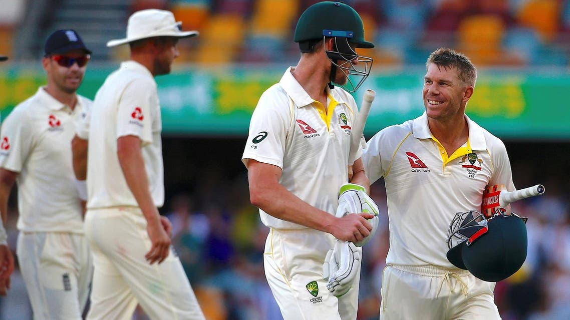England's James Anderson and Stuart Broad walk behind Australia's Cameron Bancroft and teammate David Warner at the end of the fourth day of the first Ashes cricket test match. (Reuters)