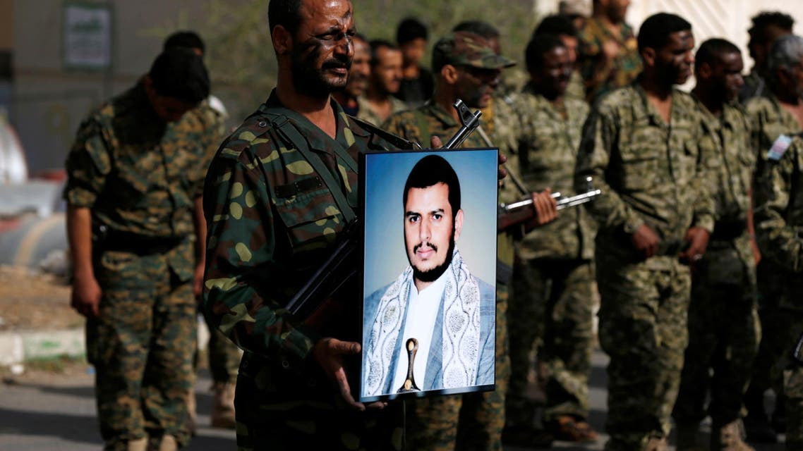 Newly recruited fighter holds a poster of the Houthi movement's leader Abdulmalik al-Houthi. (Reuters)