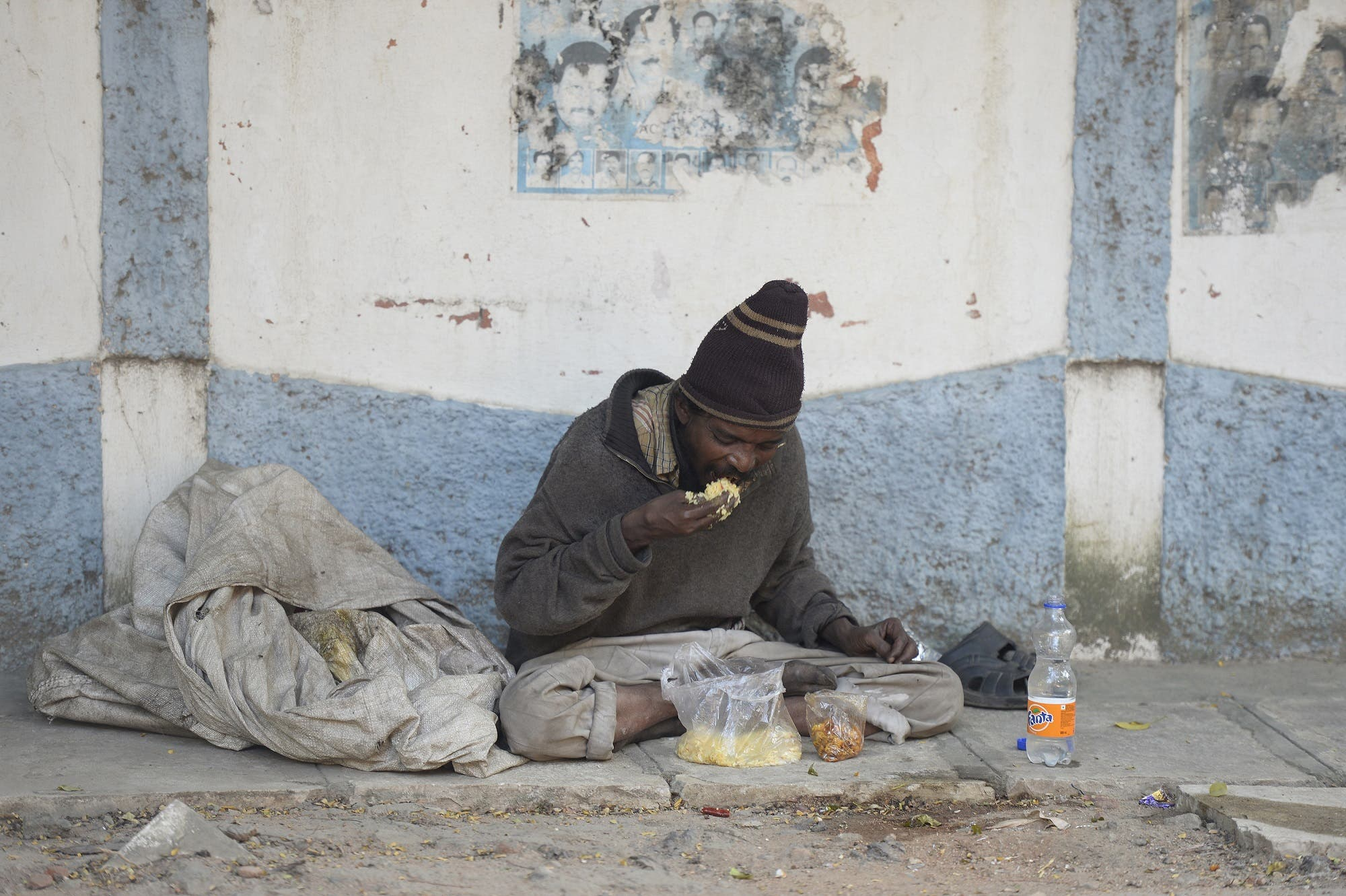 An Indian beggar eats food on the side of the road in Hyderabad on November 10, 2017. The city banned begging in public places ahead of a three-day summit that Ivanka Trump is due to attend, police said November 10. (AFP)