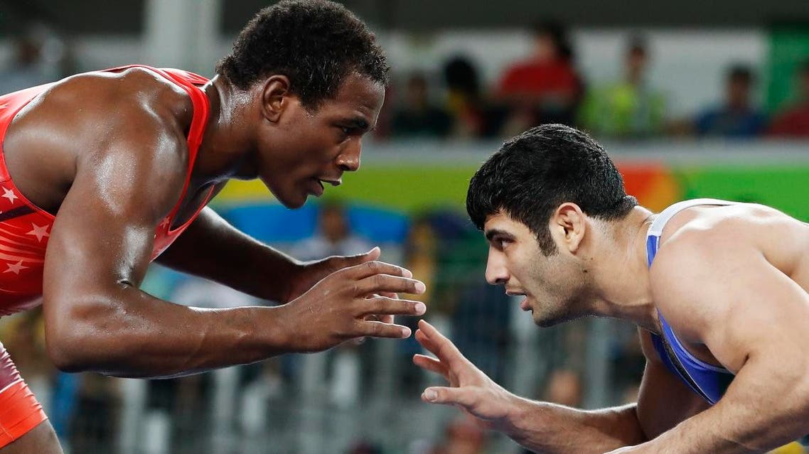 This file photo taken on August 20, 2016 shows USA's J'den Michael Tbory Cox (red) wrestling with Iran's Alireza Mohammad Karimimachiani in their men's 86kg freestyle quarter-final match. (AFP)