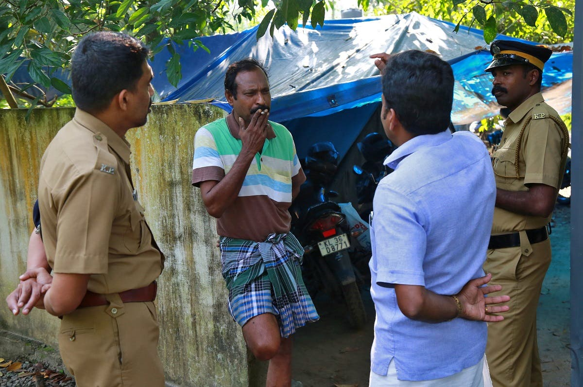 K M Ashokan (2-L), father of 24-year-old Akhila, who converted to Islam in 2016 and took a new name, Hadiya, smokes while speaking with a friend, as police officers stand guard outside his house at Vaikom in the Kottayam district of the southern state of Kerala, India. (Reuters)