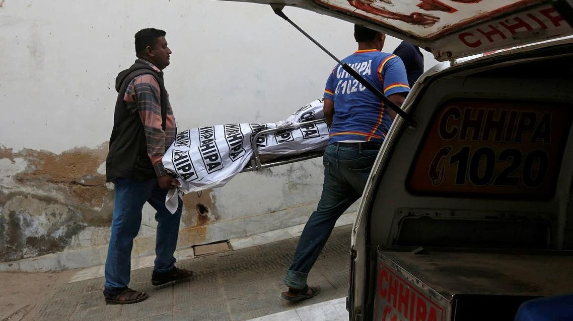 Rescue workers move one of two bodies of a couple, who according to police was killed by family members, outside hospital morgue in Karachi. (Reuters)