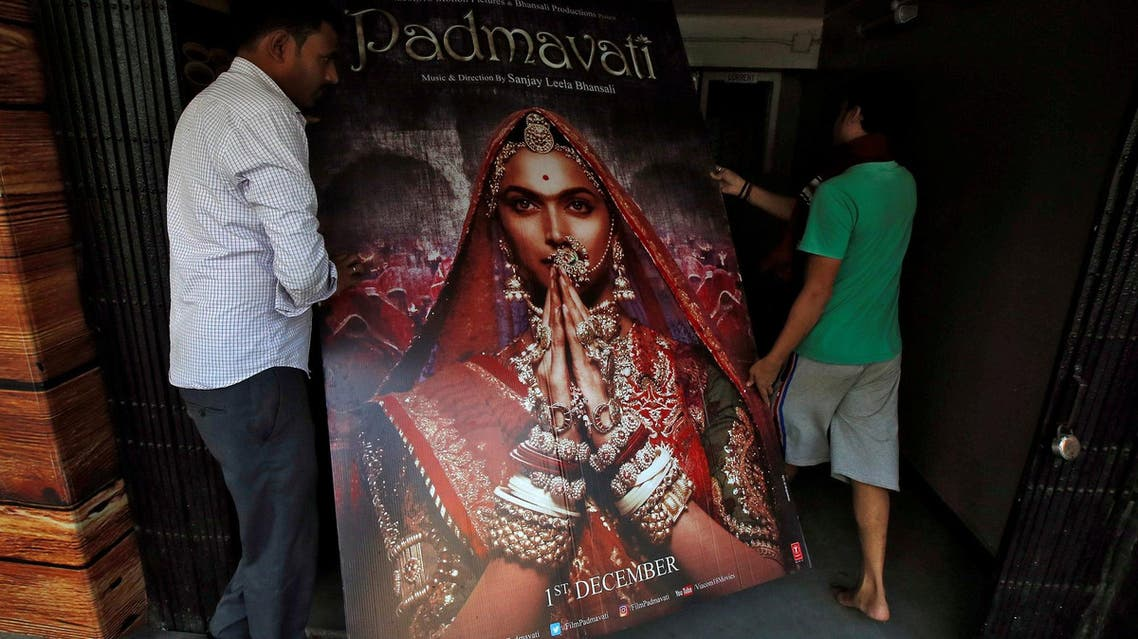 """Workers carry a poster advertising """"Padmavati"""" in a cinema hall in Kolkata on November 28, 2017. (Reuters)"""