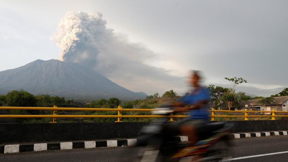 A motorist rides across a bridge as Mount Agung volcano erupts near Kubu in Bali. (Reuters)