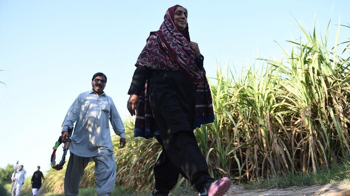 This photograph taken on September 27, 2017, shows Pakistani woman Mukhtiar Naz (R), known as Waderi Nazo Dharejo, walking her guard at her agriculture field in Qazi Ahmed in Sindh province. (AFP)