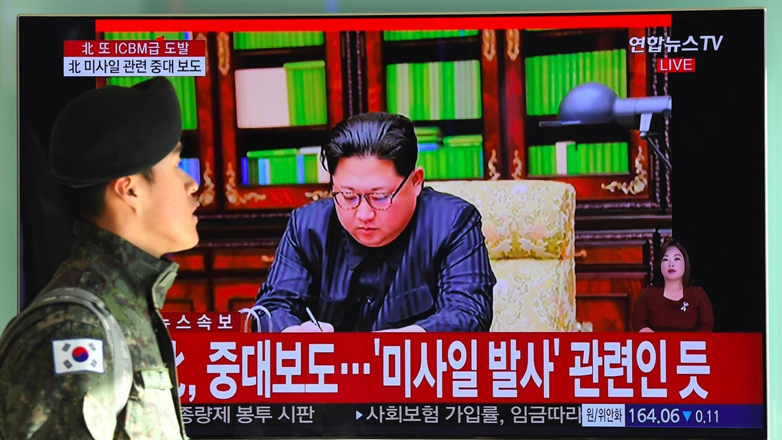 """A South Korean soldier walks past a television news screen showing North Korean leader Kim Jong-Un approving the country's new ICBM test, at a railway station in Seoul on November 29, 2017 Nuclear-armed North Korea said on November 29 it had successfully tested a new intercontinental ballistic missile that put """"all of the US continent"""" within its range.  JUNG Yeon-Je / AFP"""