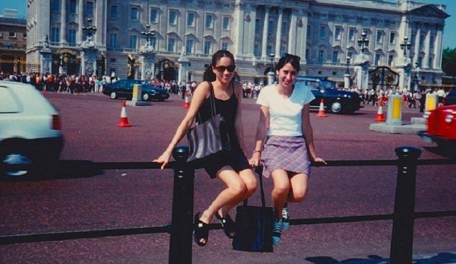 ميغان ماركل، إلى اليسار، مع من كانت أفضل صديقة لها زمن الطفولة، وهما جالستان أمام قصر باكنغهام
