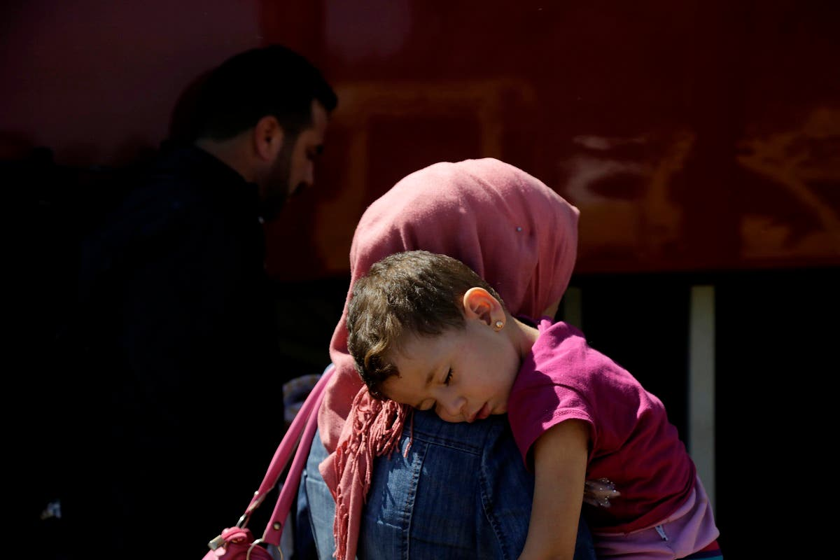 A woman with her child migrant from Syria walk towards a refugee camp at Kokkinotrimithia, outside of the capital Nicosia, in the eastern Mediterranean island of Cyprus, on Sunday, Sept. 10, 2017. (AP)