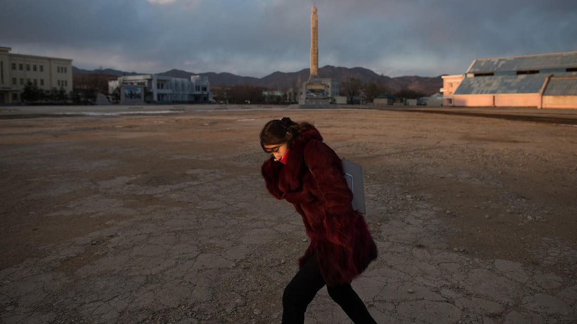 In a photo taken on November 21, 2017, a woman shields herself from the cold at the port in Rason. (AFP)