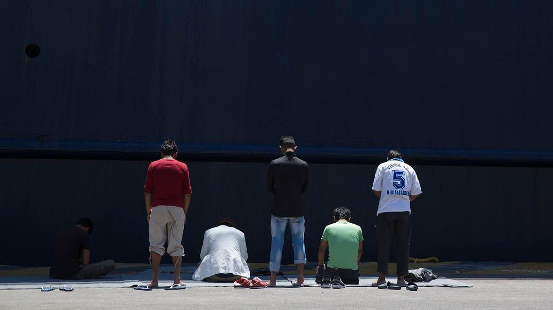 Afghan migrants stranded in Greece, pray in front of a docked ferry at the port of Piraeus , near Athens on the first day of the holy fasting month of Ramadan on Monday, June 6, 2016. (AP)