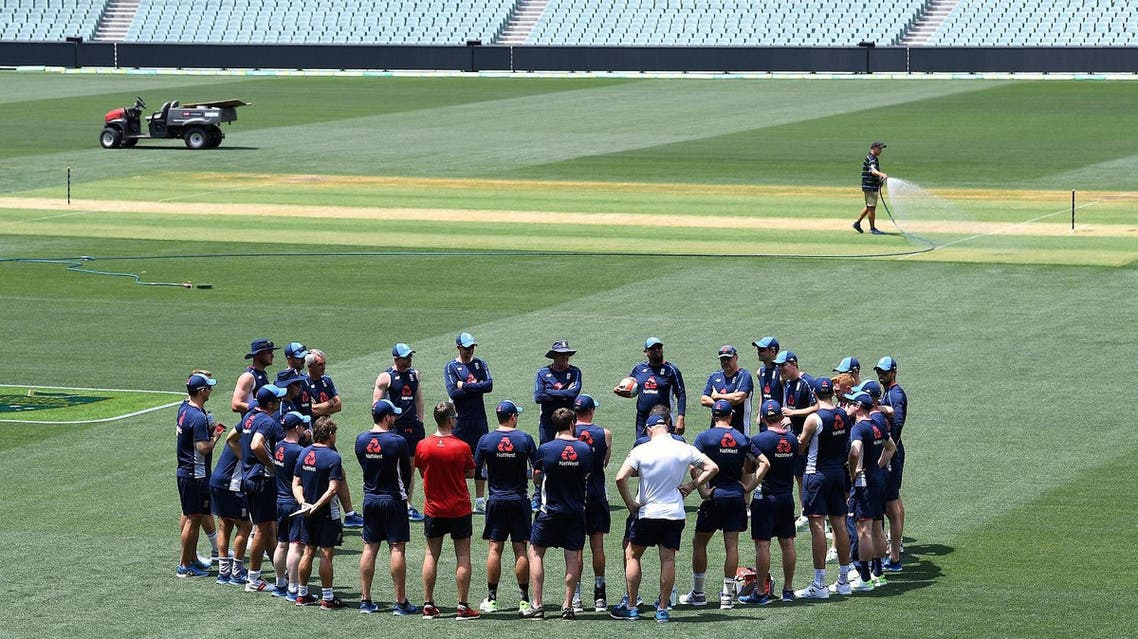 A groundsman sprays water on the pitch as England cricket team players and coaching staff stand in a circle during a training session at the Adelaide Oval. (Reuters)
