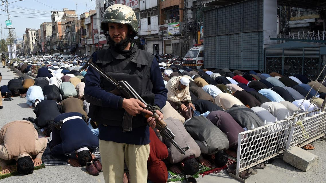 A Pakistani policeman stands guard as Muslims offer Friday prayers on a street in Peshawar on February 17, 2017. (AFP)