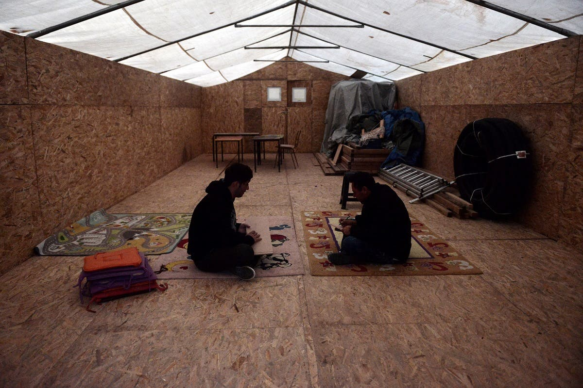 Yazidi refugees sit in a makeshift accommodation turned into a classroom at the Serres refugee camp, northern Greece, on November 24, 2017. (AFP)