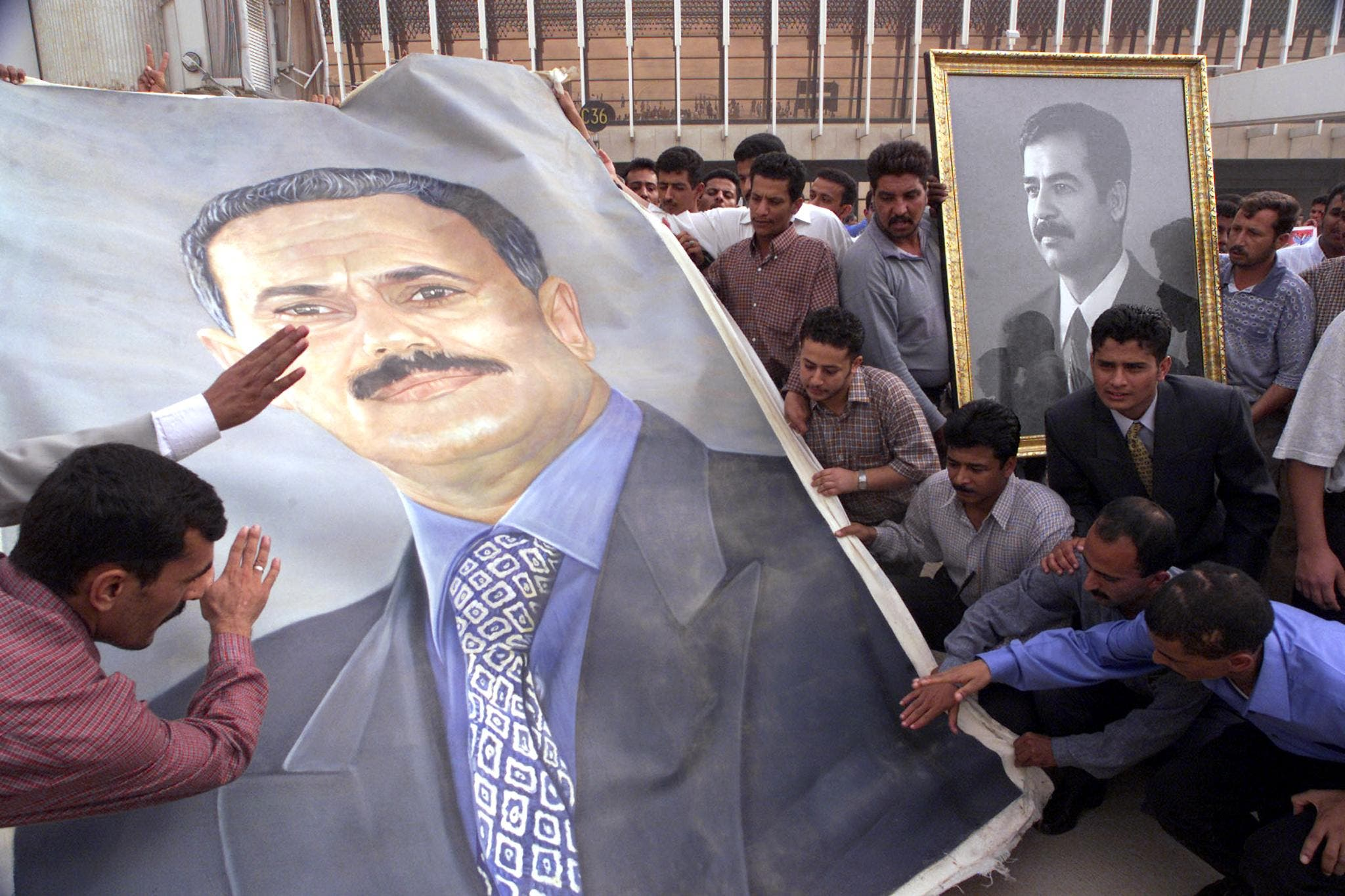 Iraqis and Yemenis hold portraits of their leaders, Saddam Hussein (R) and Ali Abdullah Saleh (L), at Saddam International Airport 29 September 2000. (AFP)