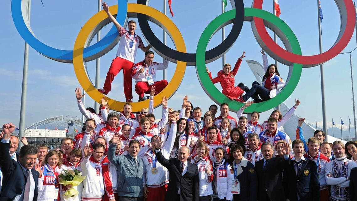 This file photo taken on February 24, 2014 shows Russia's President Vladimir Putin (center) posing for a photo with Russian athletes, winners of the Sochi 2014 Winter Olympics. (AFP)