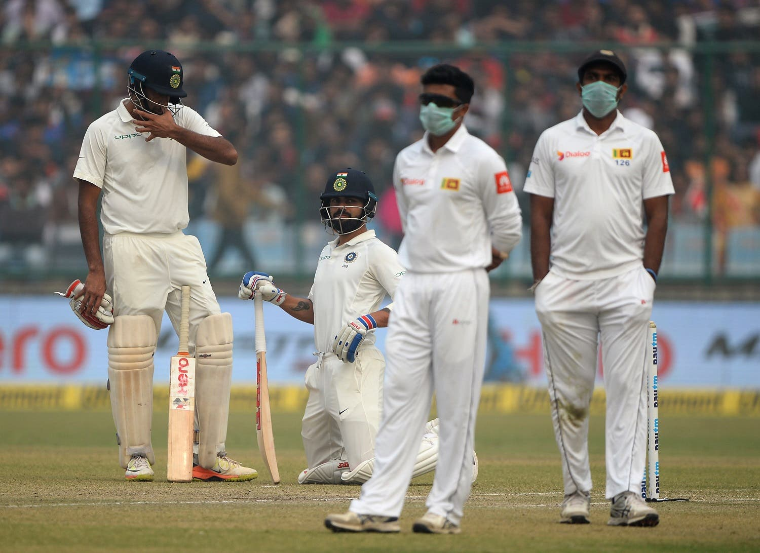 Sri Lanka cricket players wearing masks in an attempt to protect themselves from air pollution as Indian captain Virat Kohli (2L) and teammate R. Ashwin look on during the second day of the Test match in New Delhi. (AFP)