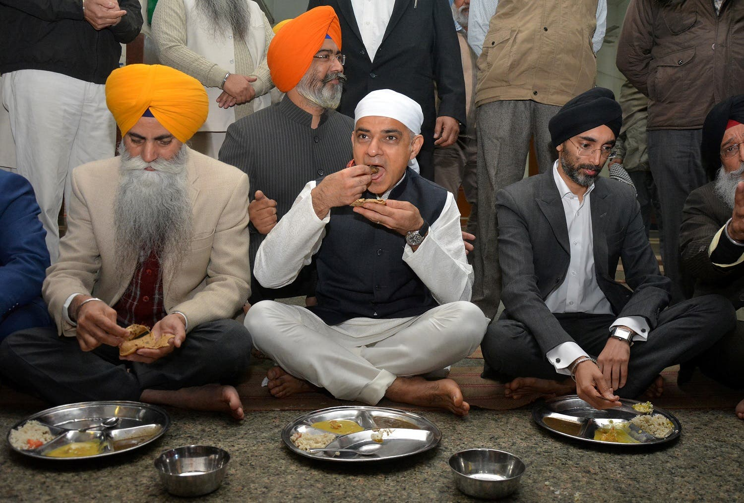 London Mayor Sadiq Khan (C) eats at a community kitchen as he visits the holy Sikh shrine of Golden temple in Amritsar, India. (Reuters)