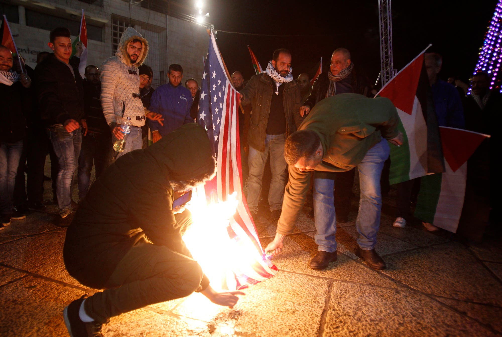 Palestinian demonstrators burn the US flag in Bethlehem's Manger Square in protest to the declaration of the US president declaring Jerusalem as Israel's capital on December 6, 2017. (AFP)