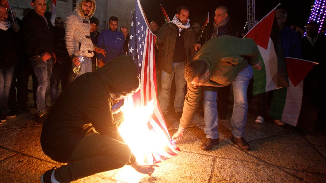 Palestinian demonstrators burn the US flag in Bethlehem's Manger Square in protest to the declaration of the US president declaring Jerusalem as Israel's capital on December 6, 2017. (AFP)