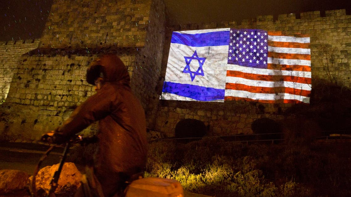 An ultra Orthodox Jewish man rides a bicycle as US and Israeli flags are projected on the walls of Jerusalem's old city, Wednesday, Dec. 6, 2017. (AP)