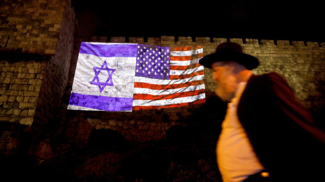 A man walks by as the Israeli national flag and an American one are projected on a part of the walls surrounding Jerusalem's Old City on December 6, 2017. (Reuters)