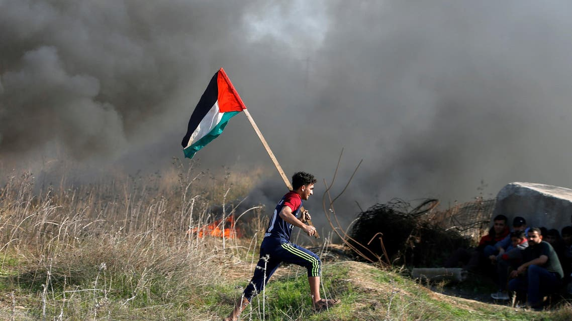 """A protester holds a Palestinian flag as he runs during clashes with Israeli troops as Palestinians call for a """"day of rage"""" in response to U.S. President Donald Trump's recognition of Jerusalem as Israel's capital, near the border with Israel in the east of Gaza City December 8, 2017. REUTERS/Mohammed Salem"""