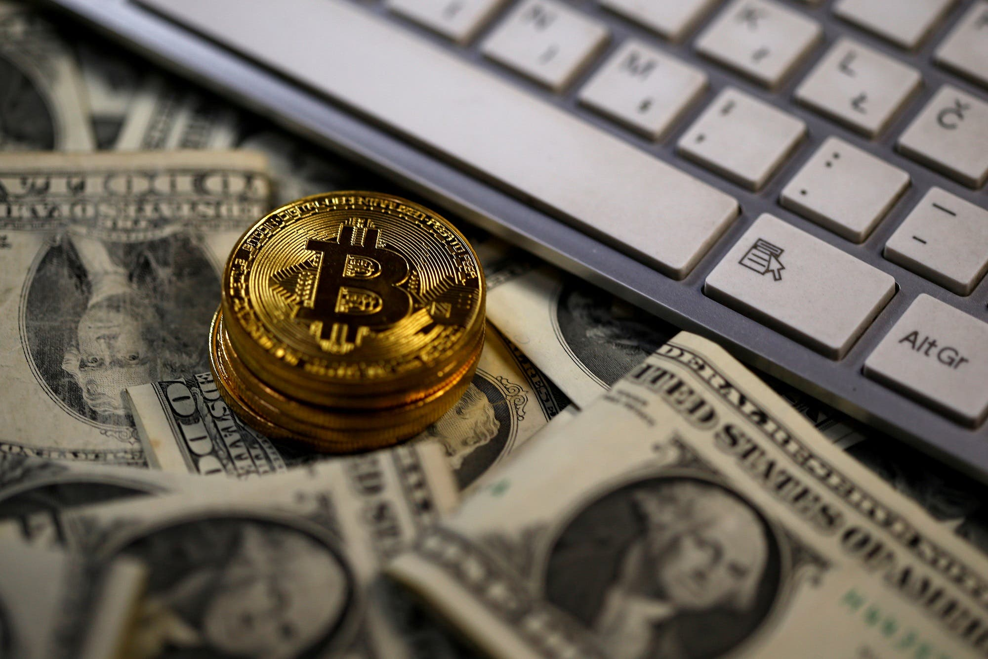 Bitcoin coins placed on Dollar banknotes, next to computer keyboard, are seen in this illustration picture, November 6, 2017. (Reuters)