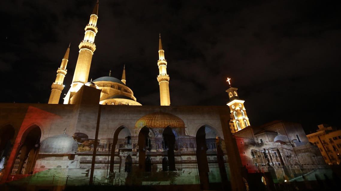 Mohammed al-Amin mosque and the Christian Maronite cathedral in Beirut illuminated with a photograph of al-Aqsa mosque on December 7, 2017. (AFP)