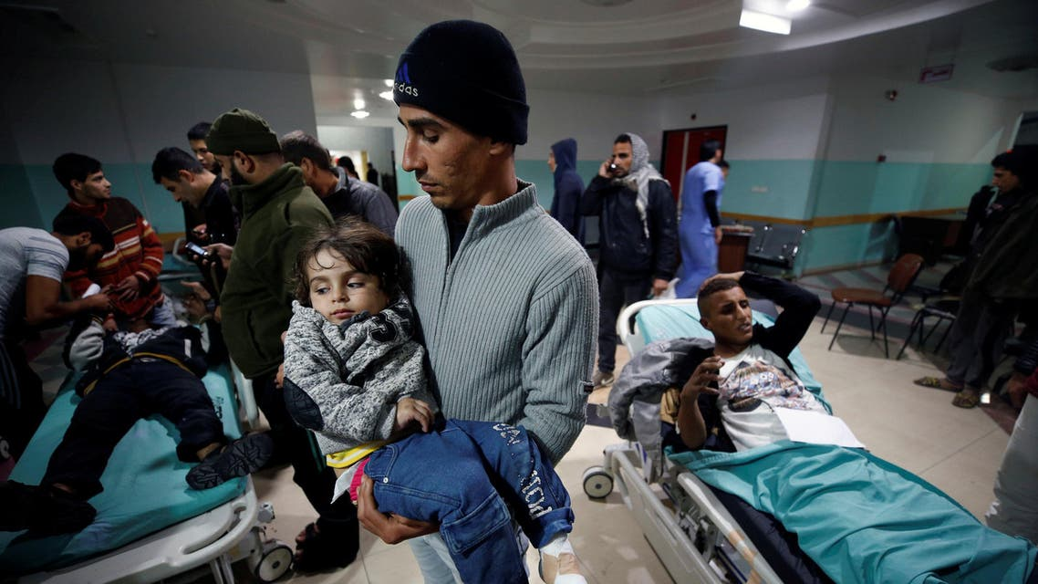 A Palestinian man carries his wounded daughter as she waits to receive treatment following Israeli airstrikes on nearby militant targets, at a hospital in the northern Gaza Strip December 8, 2017. REUTERS/Mohammed Salem