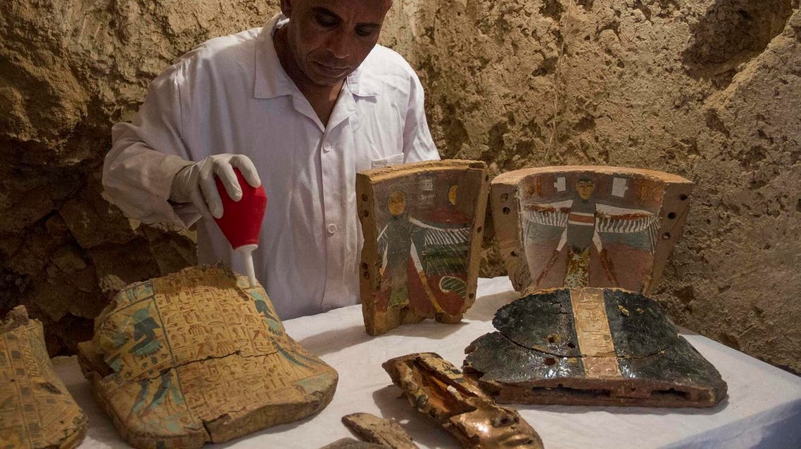 """An Egyptian excavation worker restores funeral furniture found in a newly discovered tomb on Luxor's West Bank known as """"KAMPP 161"""" during an announcement for the Egyptian Ministry of antiquities about new discoveries in Luxor, Egypt, Saturday, Dec. 9, 2017. (AP)"""