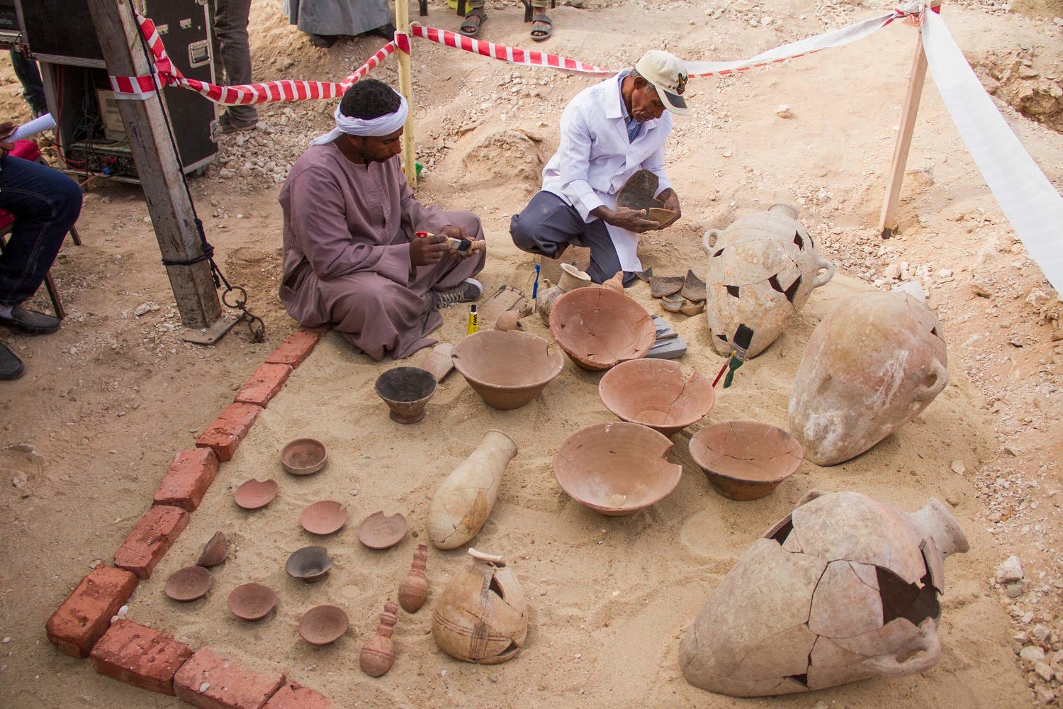 The ministry said Saturday that one tomb has five entrances leading to a rectangular hall, and contains painted wooden funerary masks, clay vessels and a mummy wrapped in linen. (AP)