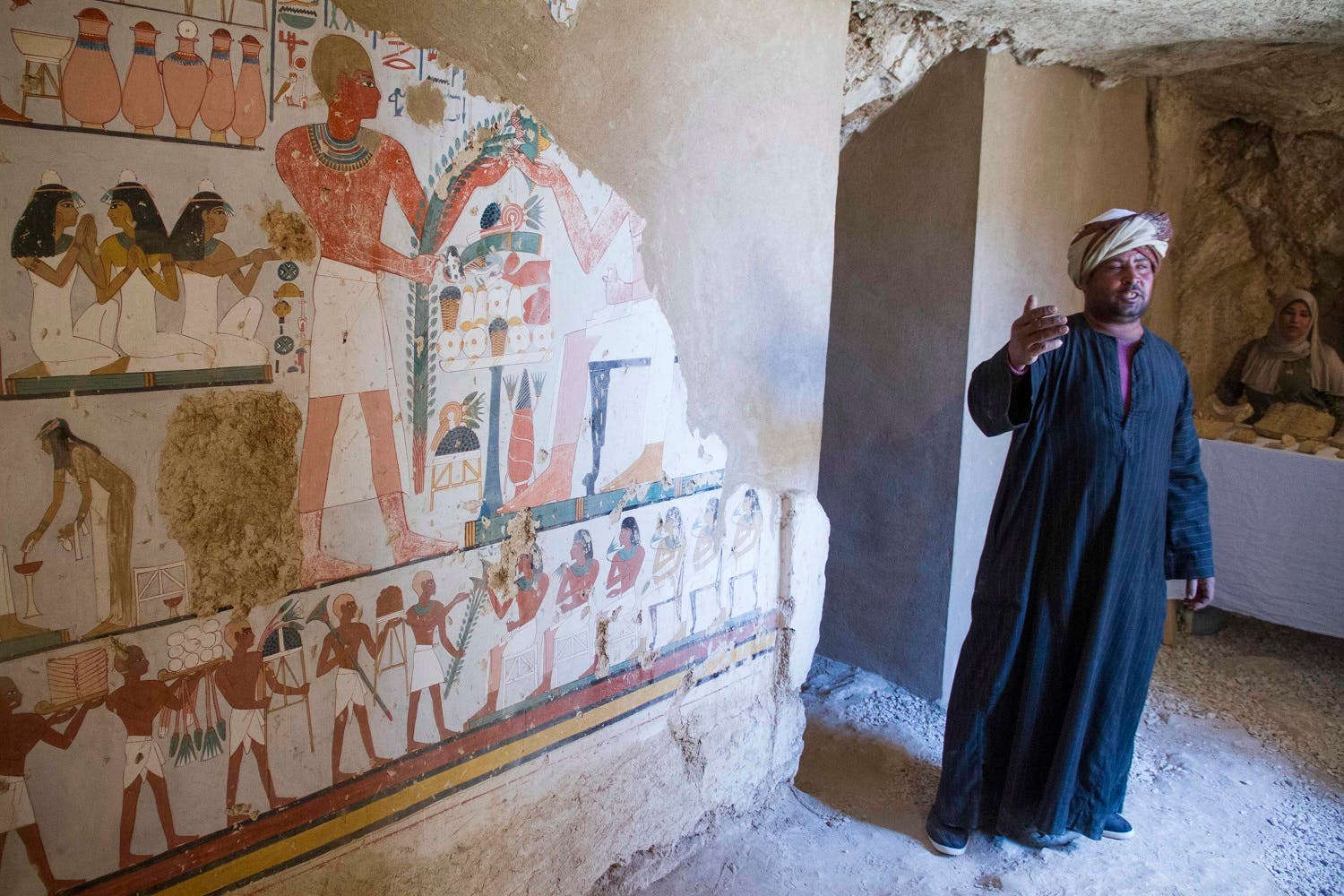 """An Egyptian guard stands next to a funeral mural inside a newly discovered tomb on Luxor's West Bank known as """"KAMPP 161"""". (AP)"""