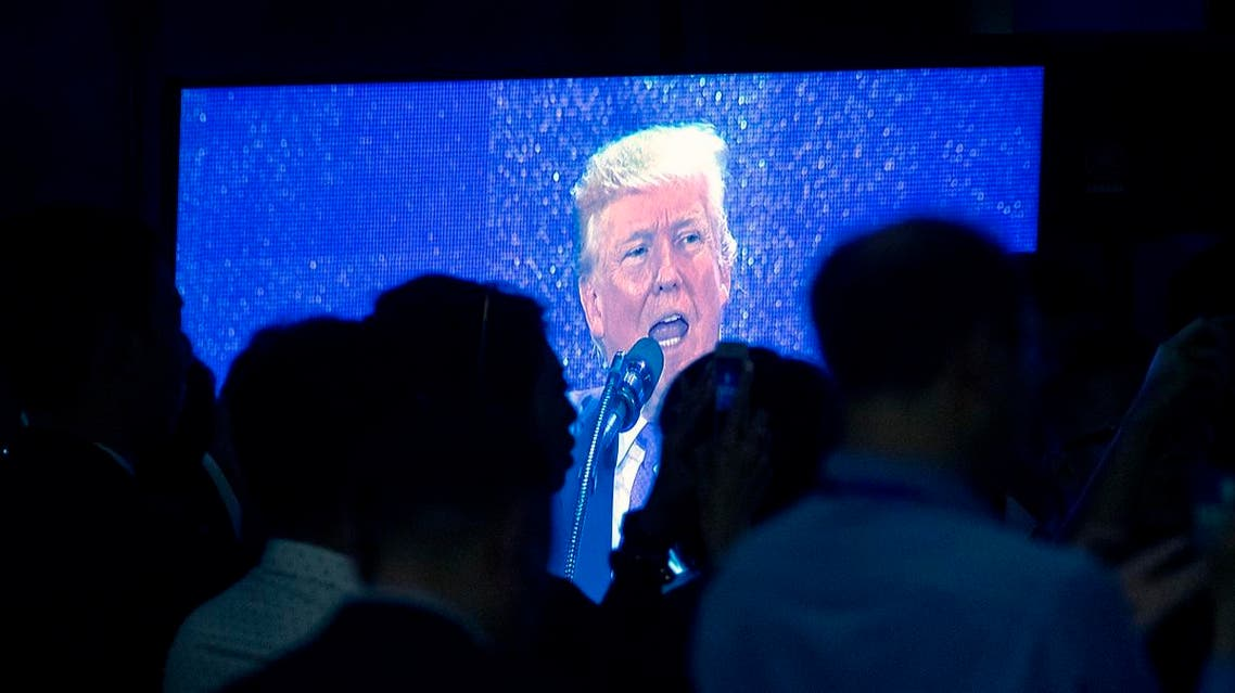 Attendees watch as U.S. President Donald Trump is shown speaking on a television monitor at the Asia-Pacific Economic Cooperation (APEC) CEO Summit at the Aryana Convention Center in Danang, Vietnam, Friday, Nov. 10, 2017. (AP)