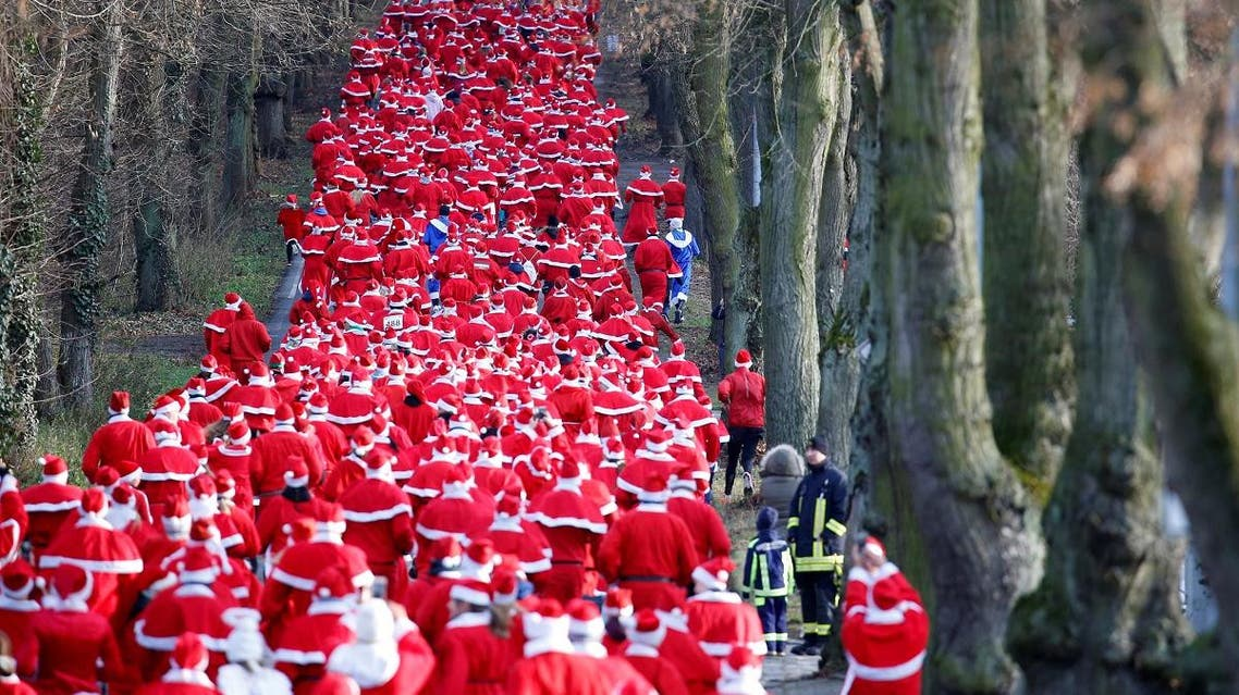 People dressed as Santa Claus run through the streets of Michendorf. (Reuters)