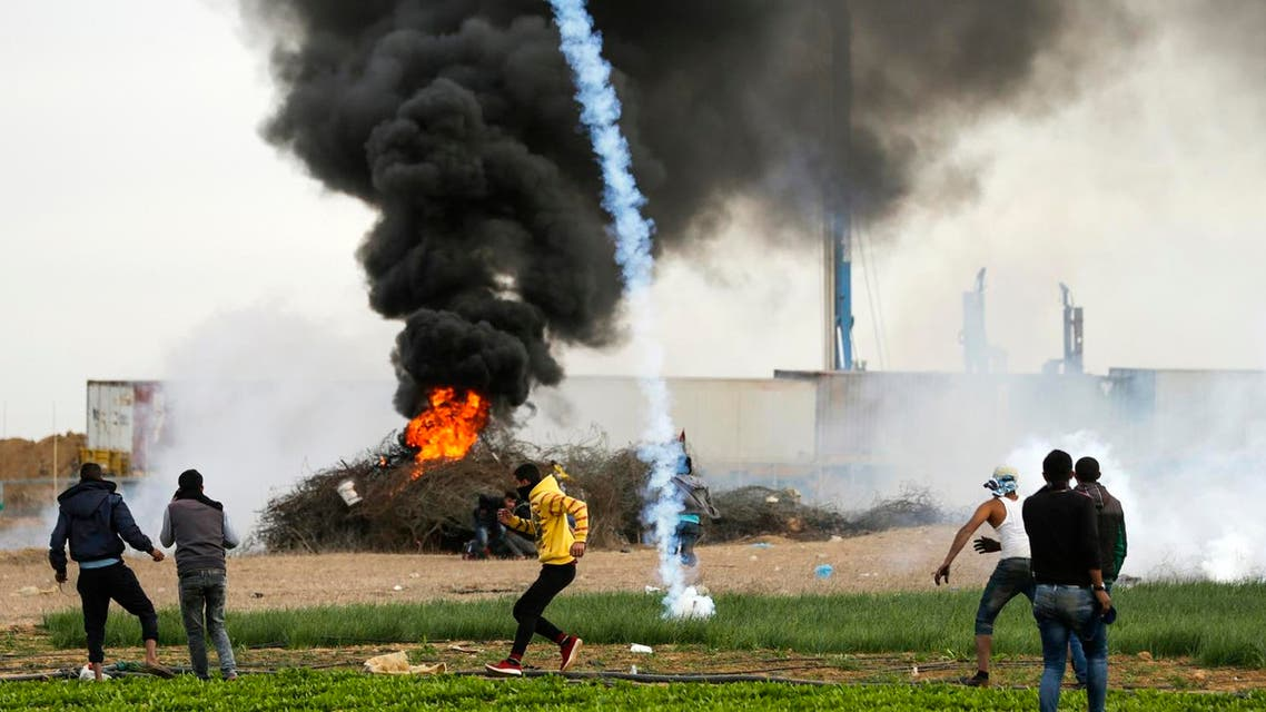 A picture taken on December 10, 2017 shows a tear gas cannister falling amdist Palestinian protesters during clashes with Israeli forces near the Israel-Gaza border. (AFP)