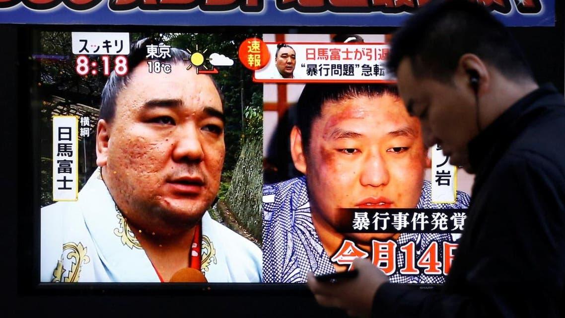 People walk past a street monitor showing Sumo grand champion Harumafuji (L) and junior wrestler Takanoiwa in Tokyo. (Reuters)