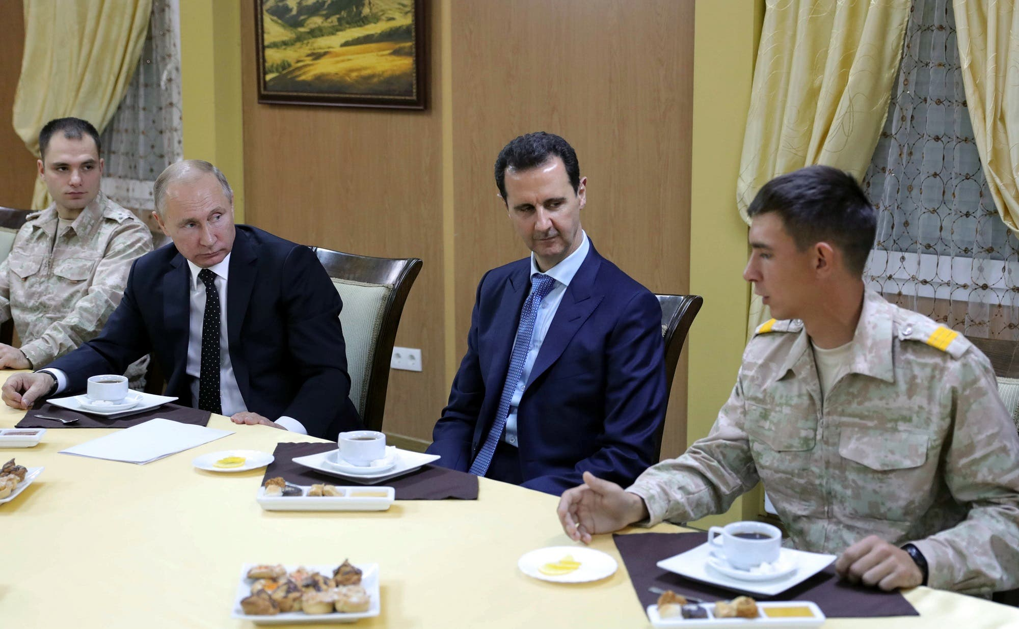 President Putin and Bashar al-Assad with Russian military officers at the Russian air base in Hmeimim, Latakia, on December 11, 2017. (AFP)