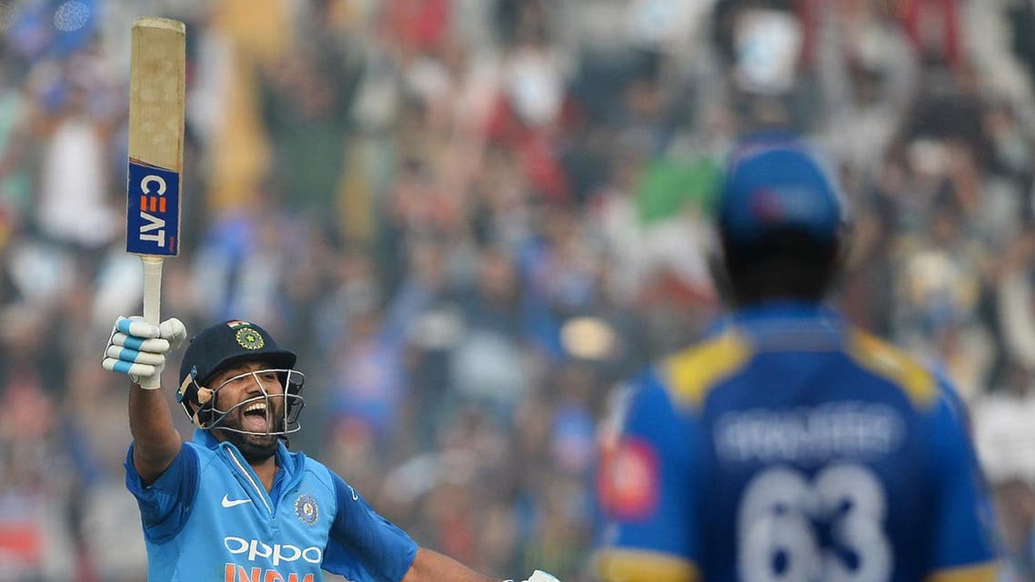 Indian cricket batsman and team captain Rohit Sharma celebrates after completing his double century (200 runs) during the second One Day International (ODI) cricket match between India and Sri Lanka in Mohali on December 13, 2017. (AFP)