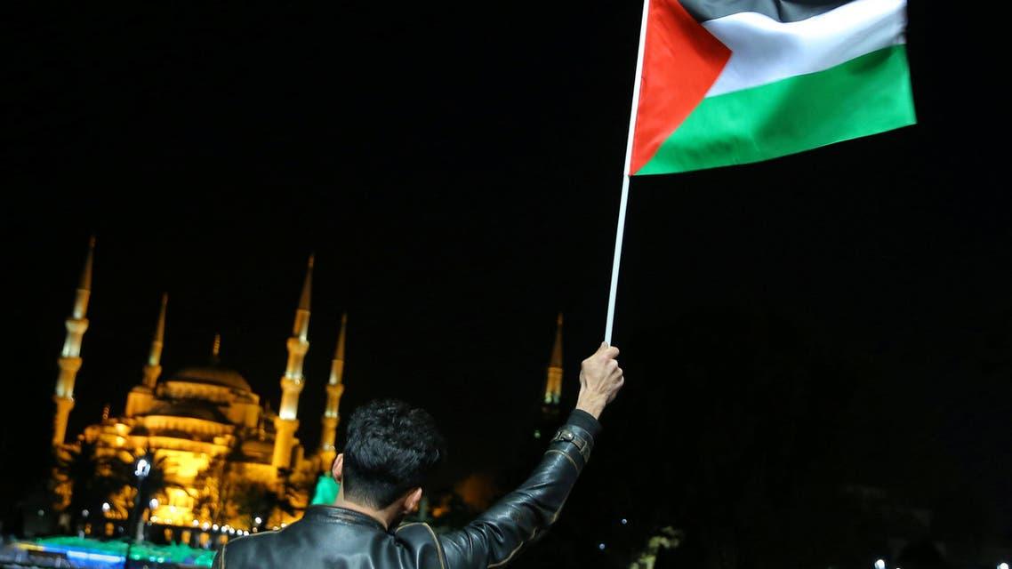 متظاهر ضد القرار الأميركي يرفع العلم الفلسطيني بمدينة اسطنبول