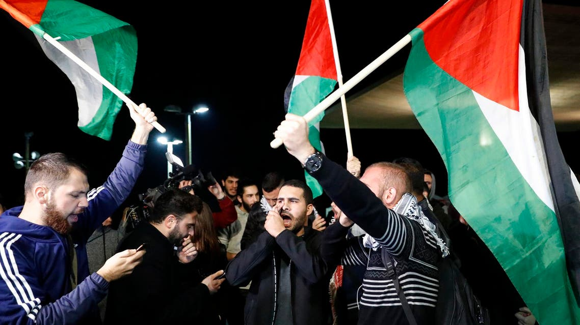 Arab-Israeli protesters wave Palestinian flags during a demonstration in front the American Embassy in Tel Aviv on December 12, 2017. (AFP)