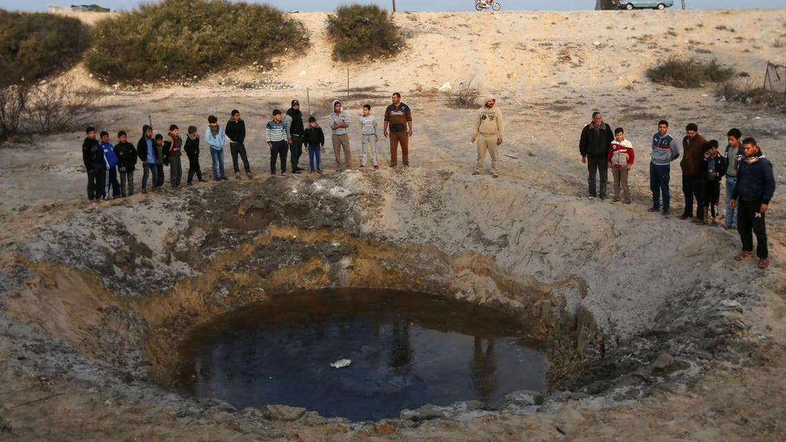 Palestinians gather at the site of an Israeli airstrike in the southern Gaza Strip December 13, 2017. REUTERS/Ibraheem Abu Mustafa
