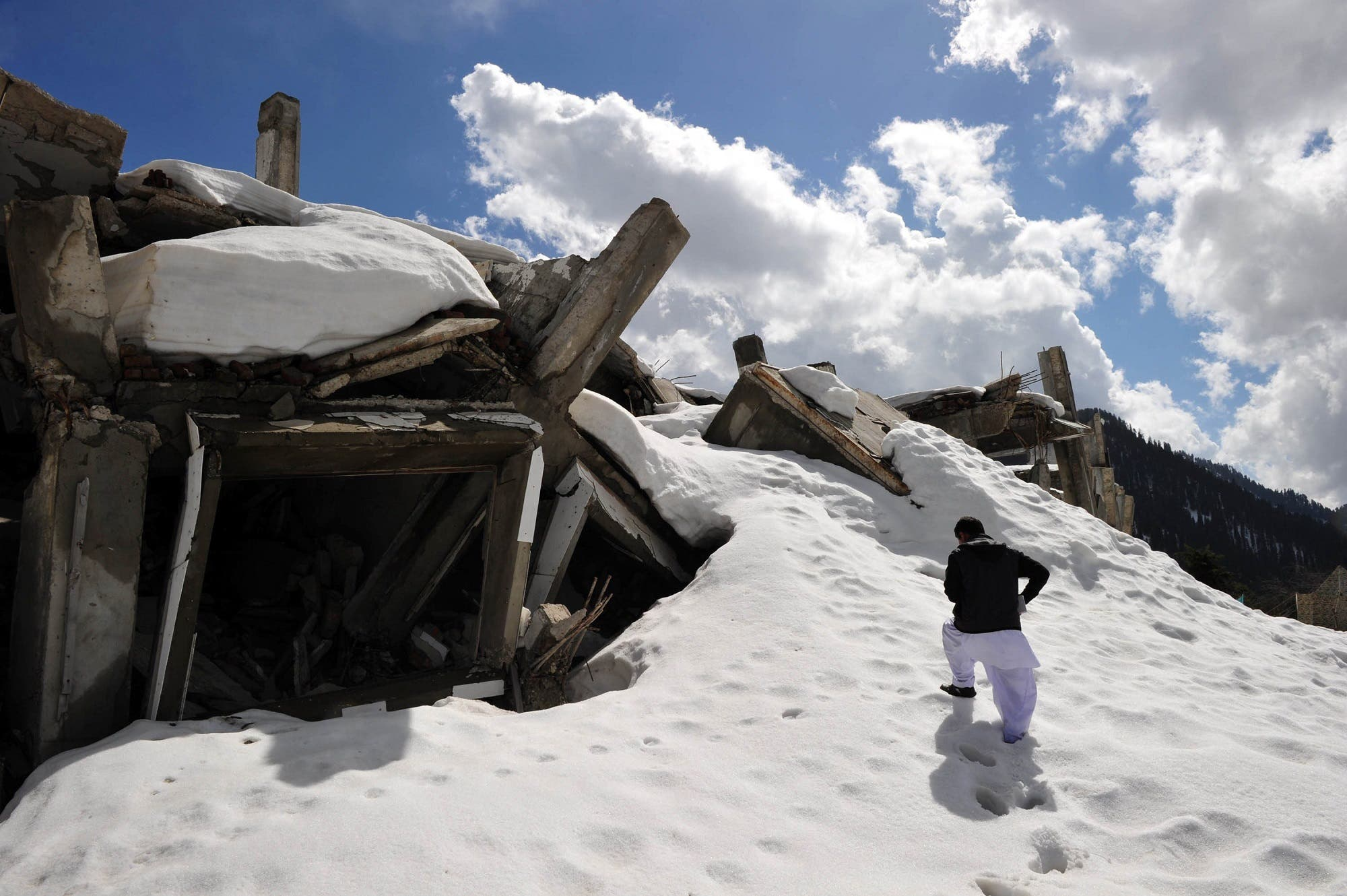This March 20, 2011 photo shows a Pakistani man walking over part of the snow-covered destroyed 72-room hotel in the mountains of the Malam Jabba resort, 300 km northwest of Islamabad in the Swat Valley. (AFP)
