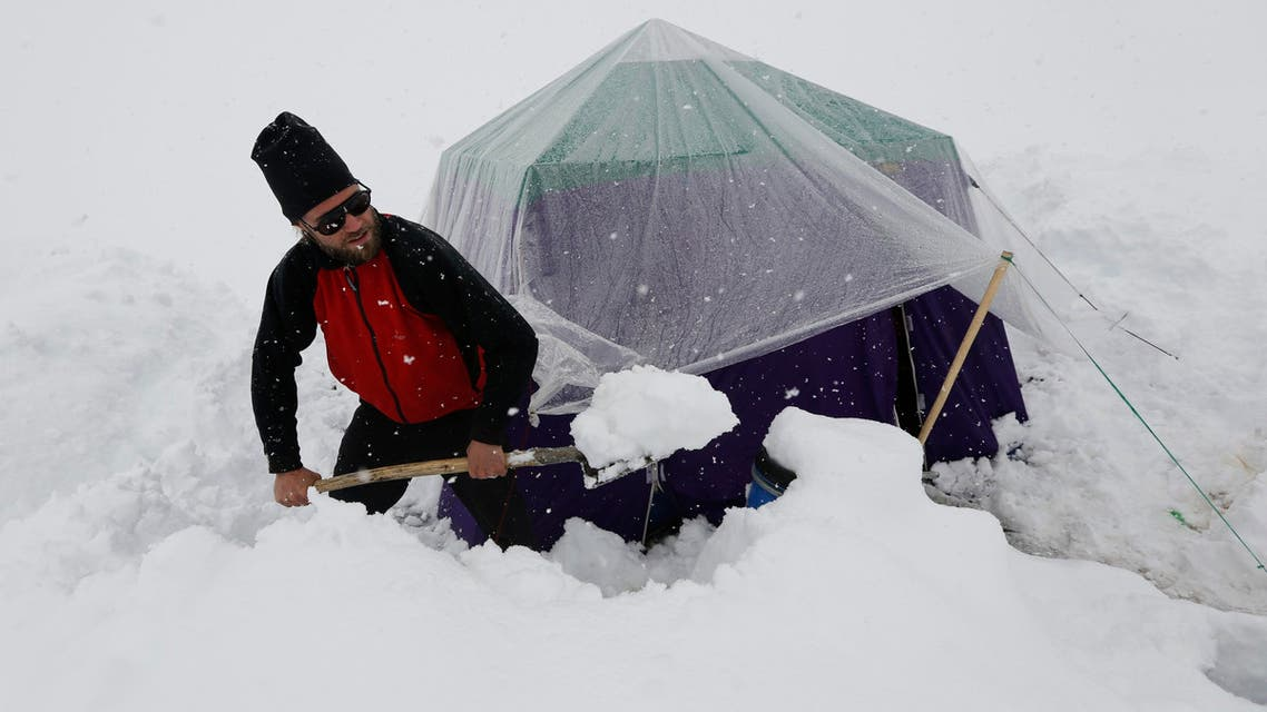 A German trekker removes snow from a kitchen tent at Concordia near the world's second highest mountain K2 in the Karakoram mountain range in Pakistan on September 5, 2014. (Reuters)