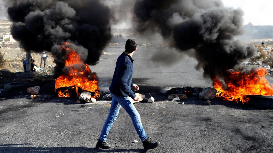 A Palestinian protester walks in front of a burned barricade during a protest near the Jewish settlement of Beit El on December 14, 2017. (Reuters)