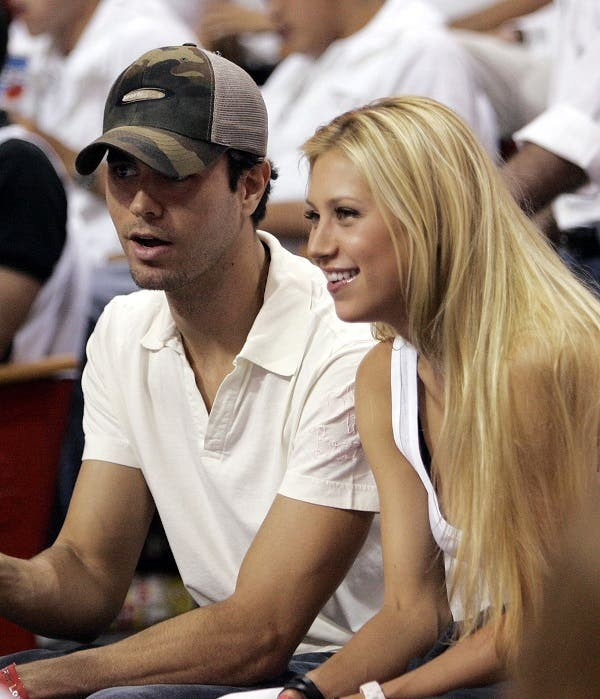 Enrique Iglesias and Anna Kournikova look on during Game 3 of the NBA basketball finals between the Dallas Mavericks and the Miami Heat in Miami, Tuesday, June 13, 2006. (AP)