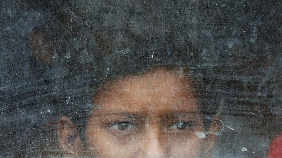 A child labourer looks out from a vehicle after being rescued during a joint operation by police and a non-governmental organisation (NGO) on World Day Against Child Labour in New Delhi June 12, 2009. (Reuters)