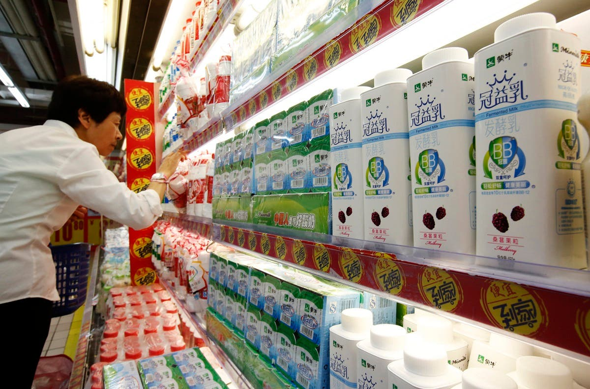 A customer shops near Mengniu's dairy products (R) displayed on shelves at a supermarket in Beijing June 19, 2013. (Reuters)