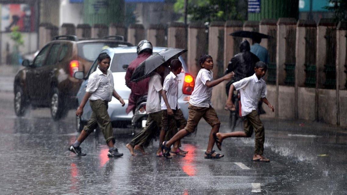 Indian school students run along a street under monsoon rains in Chennai on October 30, 2017. (AFP)