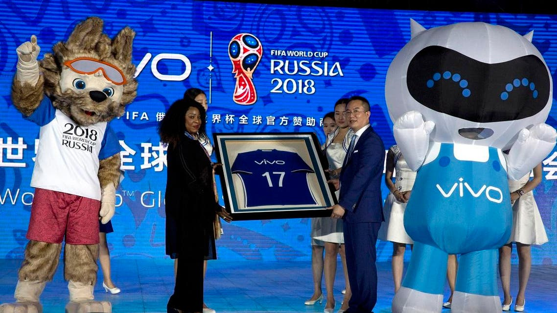 Senior Vice President of Vivo, Ni Xudong, at right holds up a jersey with FIFA's Secretary General, Fatma Samoura during a ceremony to announce the Chinese smartphone brand Vivo's sponsorship of the FIFA soccer World Cup at the Imperial Ancestral Temple in Beijing, China, Wednesday, May 31, 2017. (AP)
