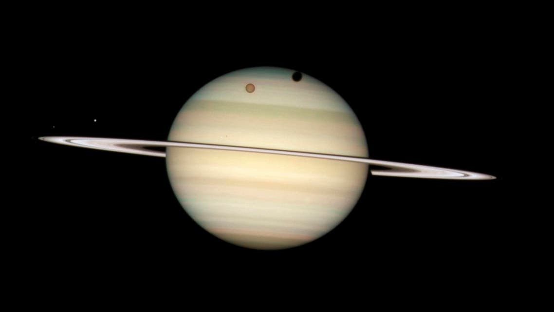 our moons of Saturn passing in front of their parent planet in seen this image taken by NASA's Hubble Space Telescope. (Reuters)